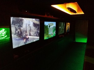 The inside of Level Up Game Truck, showing orange lit infinity mirror and 4 large gaming screens with Call of Duty.